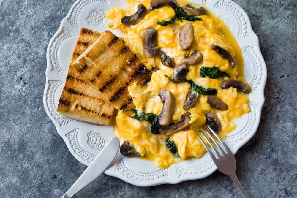 Scrambled eggs with spinach and mushrooms on a plate, along with some toast.