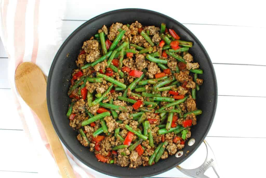 Ground pork stir fry with green beans in a large skillet next to a wooden spoon.