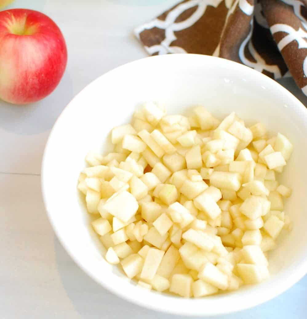 Finely chopped apples in a white bowl.