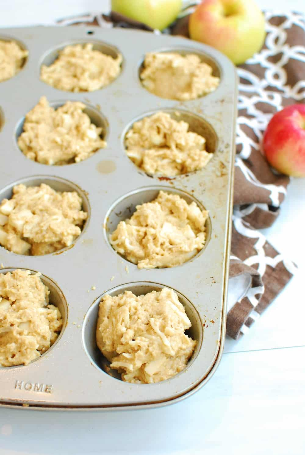 Muffin batter poured into a 12-count muffin tin.