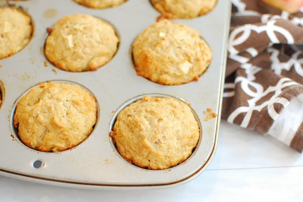A muffin tin after baking the muffins, next to a napkin.