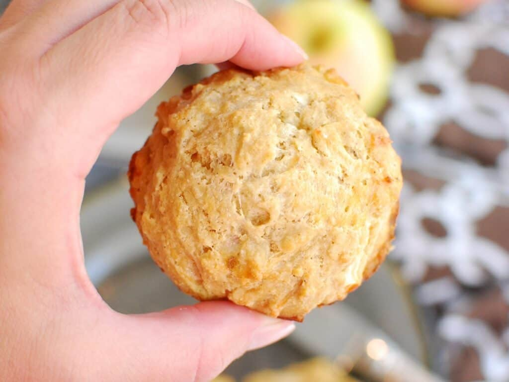 A woman's hand holding an apple cheddar muffin.