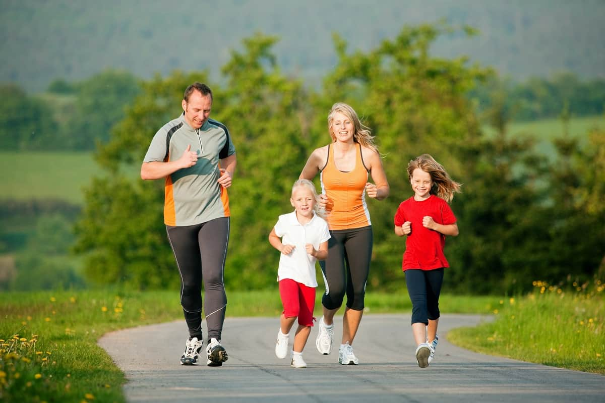A family with kids outside running on a paved path.