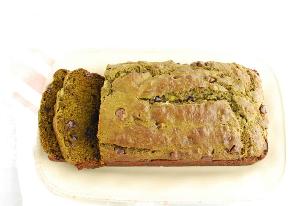 A loaf of matcha banana bread with two slices cut from the left side.