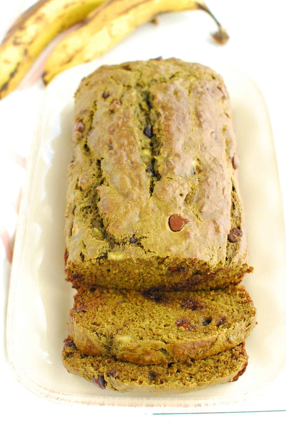 A loaf of matcha banana bread that has been sliced into, next to two overripe bananas.