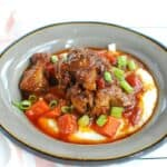 A grey bowl with oxtail and grits, along with the braising liquid stew.