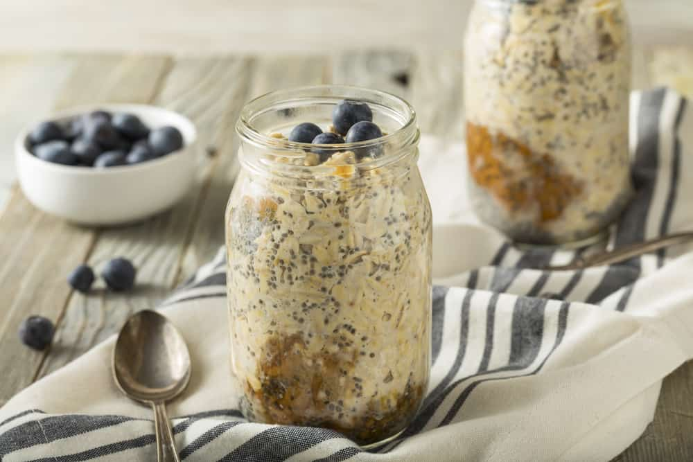 Overnight oats in a mason jar on top of a striped napkin.
