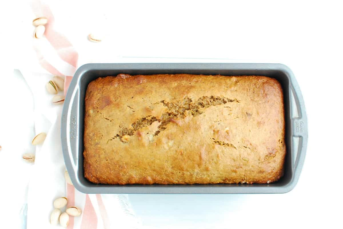 A loaf pan with a cooked loaf of pistachio banana bread.