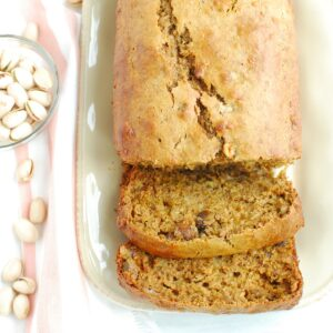 A loaf of pistachio banana bread on a plate with two slices cut.