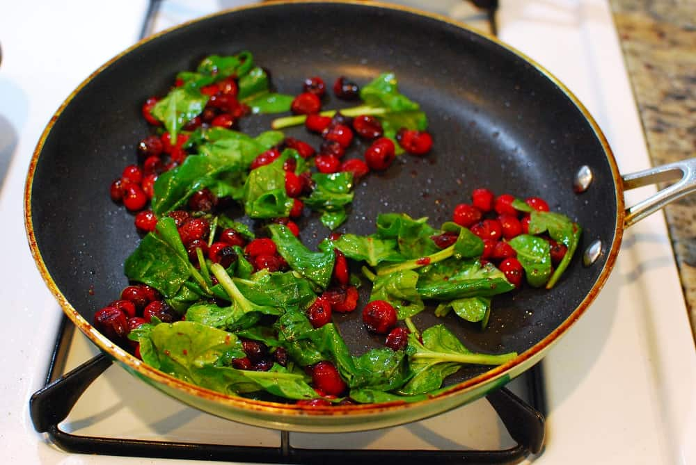 Cranberries and spinach in a sauté pan.