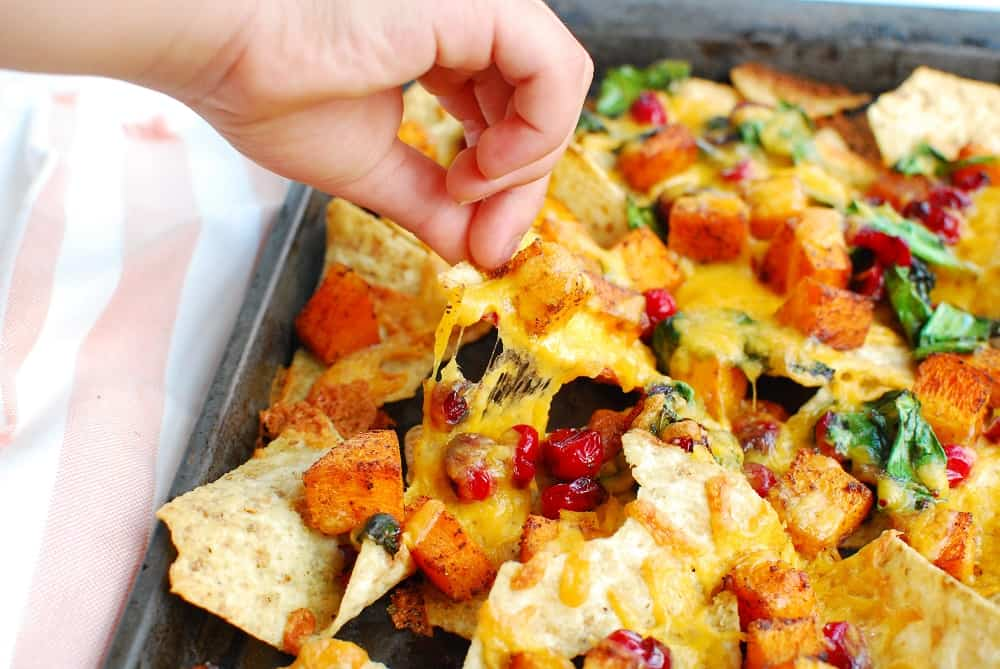 A child's hand picking up a nacho from the sheet pan.