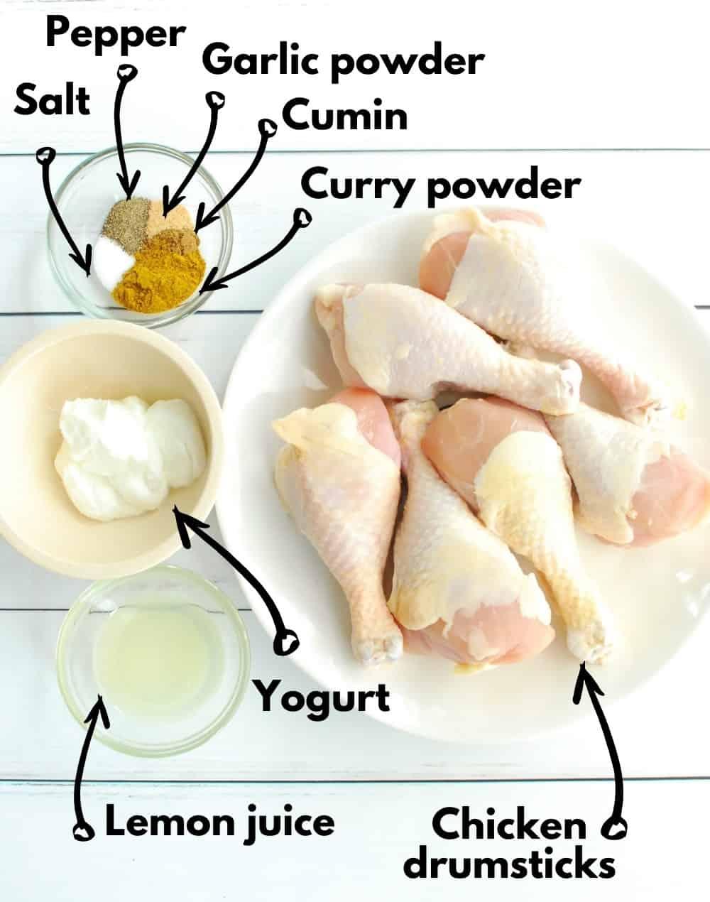 Overhead shot of chicken drumsticks, lemon juice, yogurt, and spice blend.