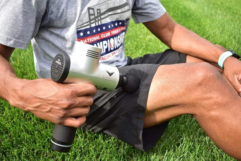 A man using a massage gun on his quads.