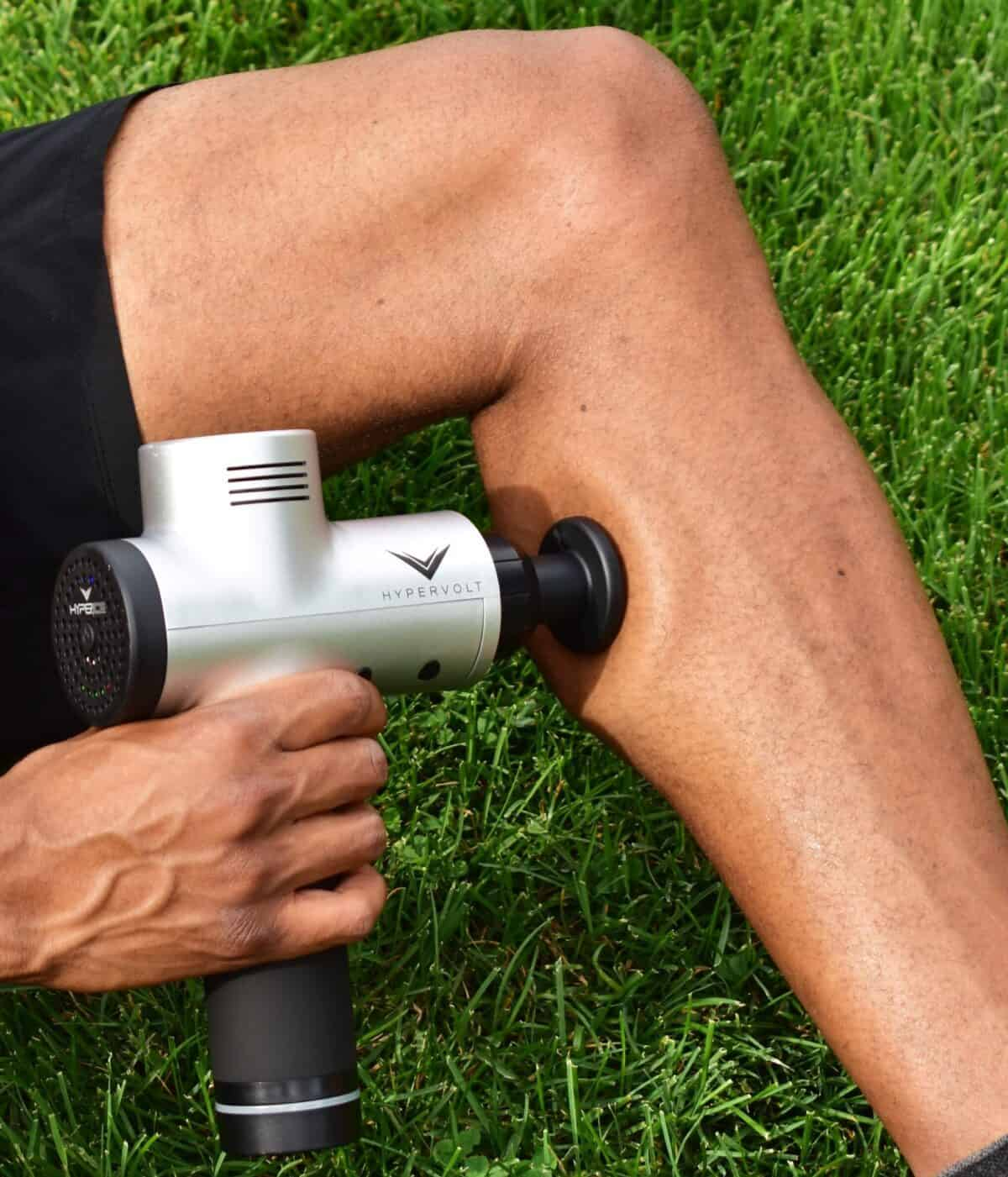 A man using a percussion massager on his calf.