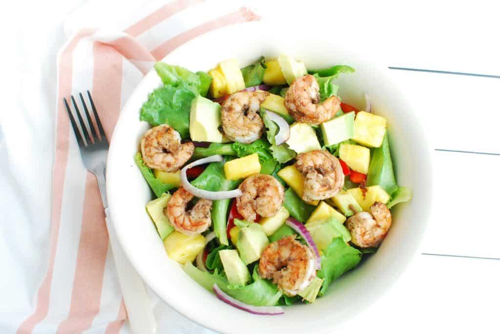 A bowl full of jerk shrimp salad next to a napkin and fork.