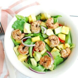 A bowl of jerk shrimp salad with lettuce, pepper, pineapple, and avocado.