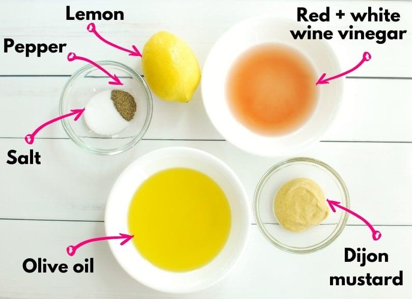 Overhead shot of olive oil, salt, pepper, lemon, vinegar, and mustard.