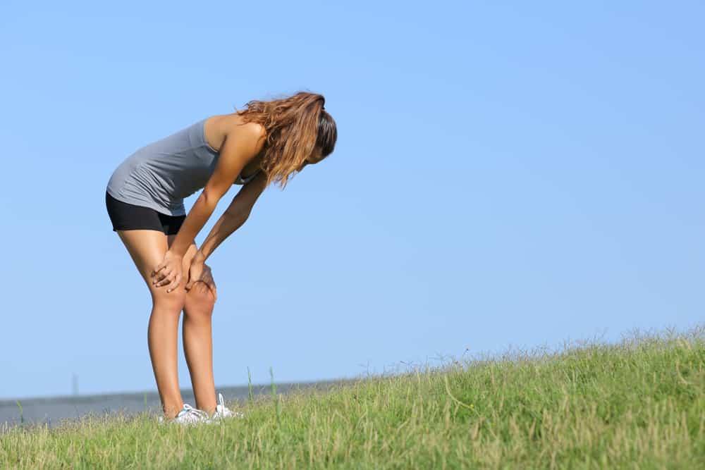 A tired female runner outside on the grass.