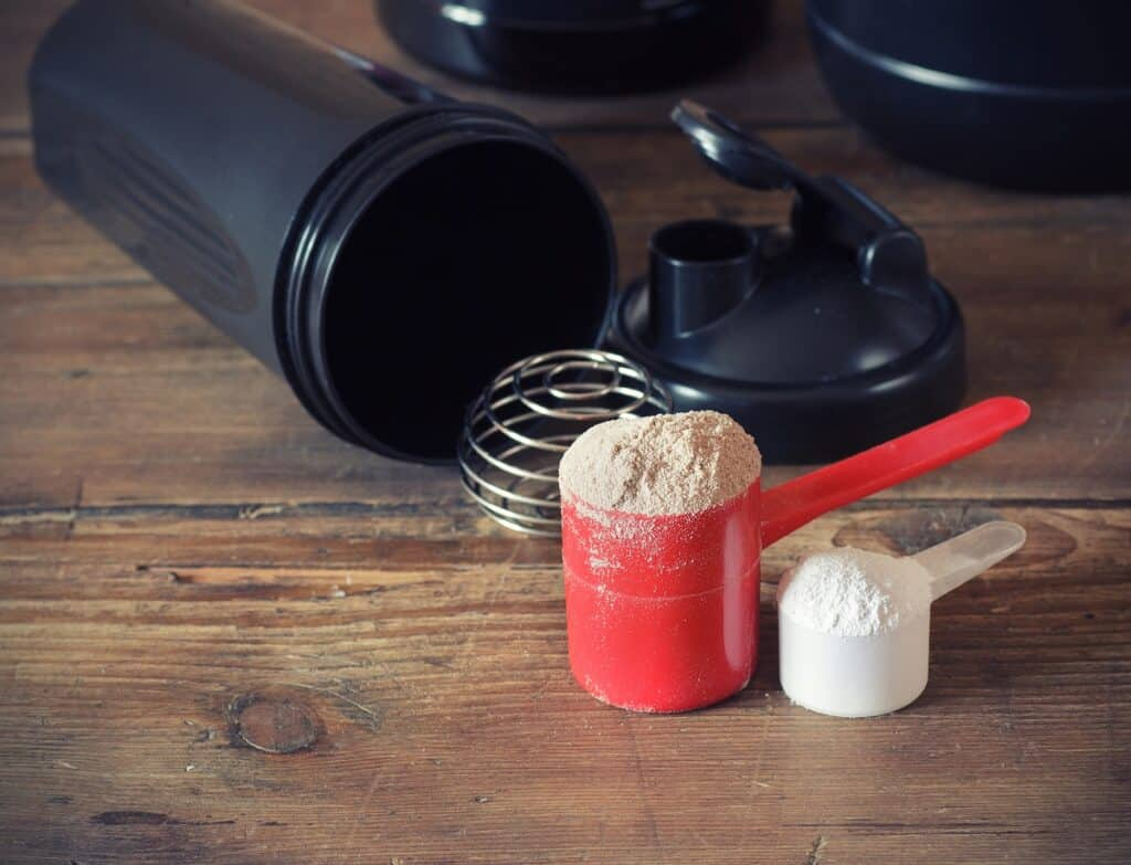 Two scoops of whey protein powder next to a shaker cup.