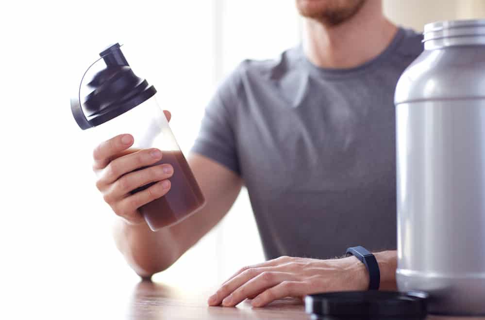 A male triathlete holding a shaker bottle with whey protein in it.