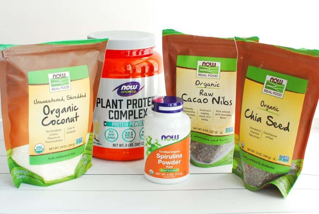 A bottle of spirulina, a container of protein powder, and bags of coconut, cacao nibs, and chia seeds.
