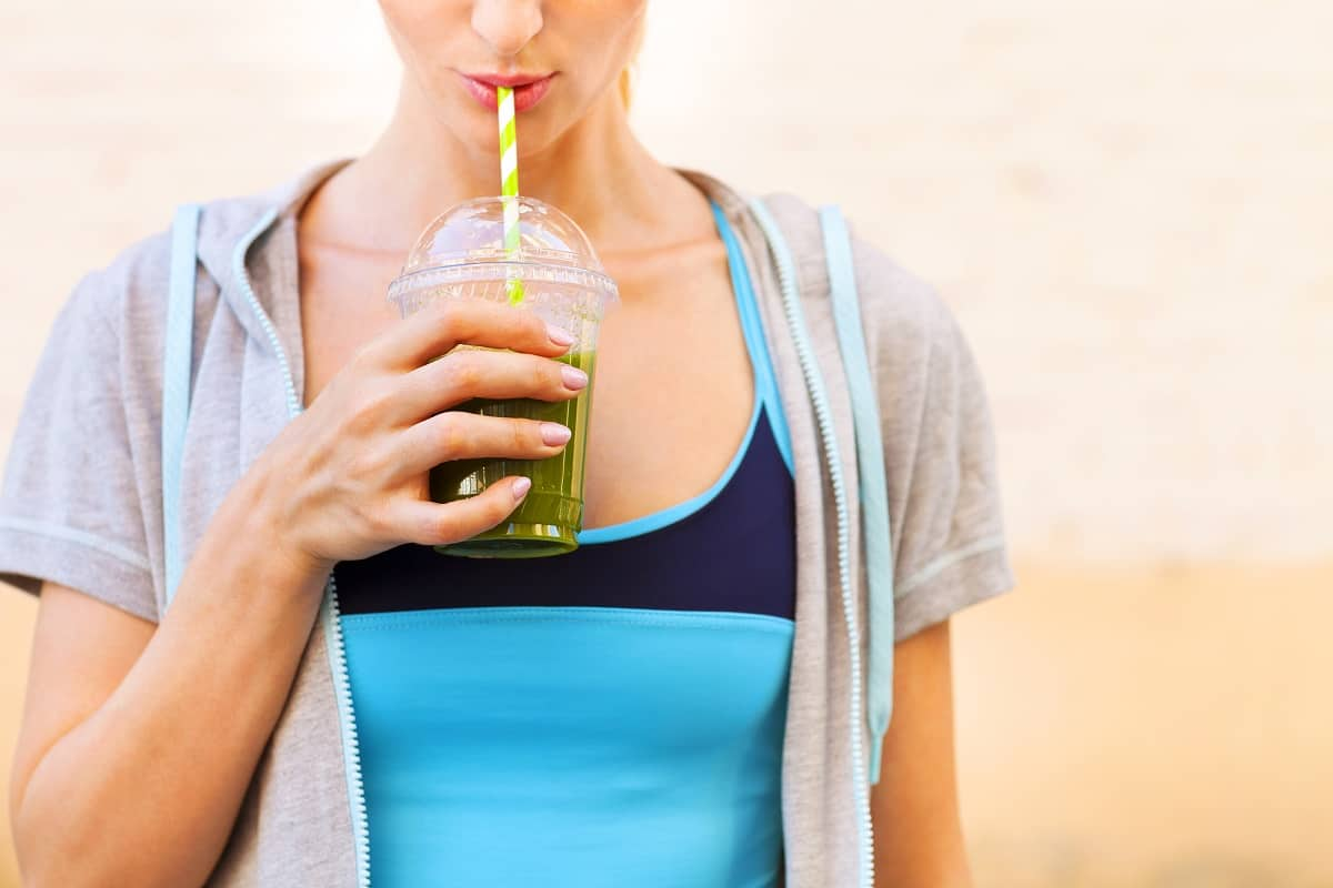 A vegan runner in athletic gear drinking a green smoothie.